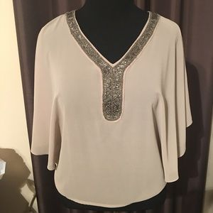 Sheer poncho top with embroidered jewelry